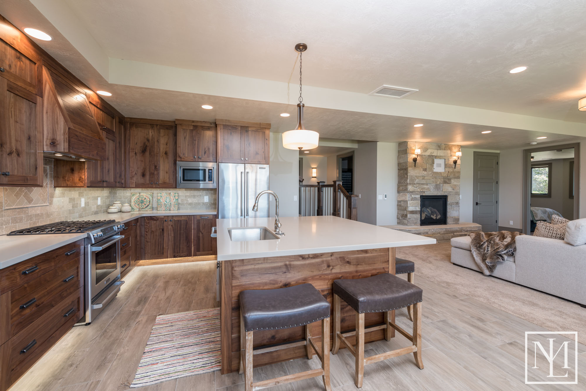 daylight floods the downstairs through the walkout and features a large gathering room with a bar theater room game room and three more bedrooms
